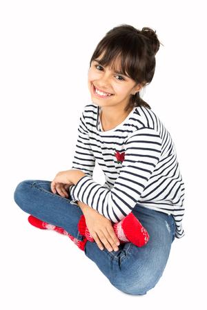 스트라이프 티셔츠와 청바지와 바닥에 앉아 빨간 양말에 작은 행복 소녀 초상화. 화이트 절연 스톡 콘텐츠