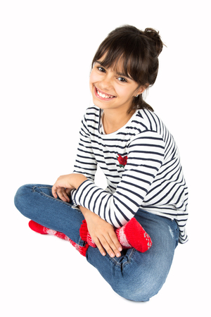 Portrait of little happy girl in striped t-shirt and blue jeans and red socks sitting on the floor. Isolated on white Фото со стока