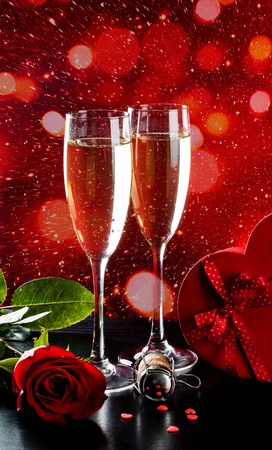 Valentines day celebration with champagne, rose and heart shaped candies. Lights bokeh at the background