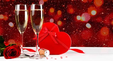 Valentinstagfeier mit Champagner, Rose, herzförmigem Geschenk und roten Süßigkeiten. Lichter Bokeh im Hintergrund Standard-Bild - 93470732
