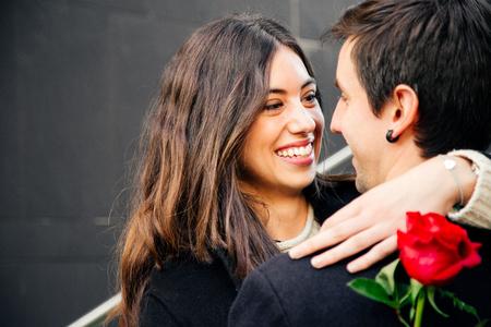 Het mooie en gelukkige paar die in liefde op de straat knuffelen die een rood houden nam liefdevol het bekijken elkaar toe