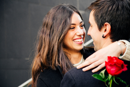 Pretty and happy couple in love cuddling on the street holding a red rose looking at each other lovingly Stockfoto