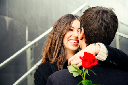 Pretty and happy couple in love cuddling on the street holding a red rose looking at each other lovingly Stockfoto - 93548090