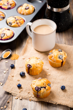 Freshly baked blueberry muffins with almond, oats and icing sugar topping on a rustic wooden table and a mug of coffee. Stock Photo