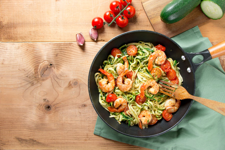 Zucchini spaghetti sauteed with tomato cherry and prawns in a pan on a rustic wooden table. Top view Standard-Bild