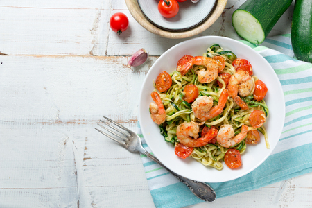 Zucchini noodles sauteed with tomato cherry and prawns in a dish on a rustic white wooden table. Top view