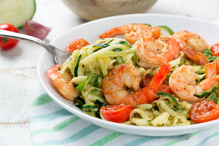 Zucchini noodles sauteed with tomato cherry and prawns in a dish on a rustic white wooden table. Close up