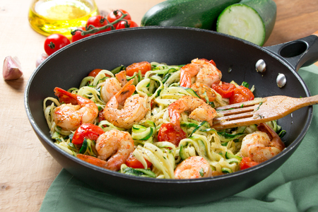 Zucchini spaghetti sauteed with tomato cherry and prawns in a pan on a rustic wooden table. Close up Stockfoto