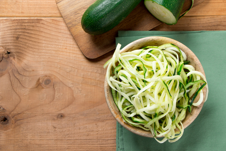 Raw zucchini noodles in a wooden bowl on a rustic wooden table. Top view