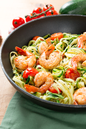 Zucchini spaghetti sauteed with tomato cherry and prawns in a pan on a rustic wooden table. Close up Stock Photo