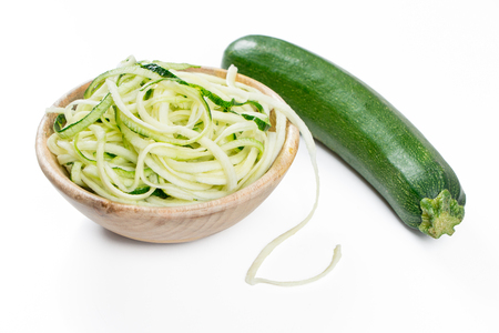 Raw zucchini noodles in a rustic wooden bowl isolated on white Zdjęcie Seryjne
