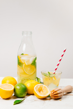 Natural lemonade with lemon, lime and mint in a bottle with wooden reamer and lemon tree leaves on a white wooden table