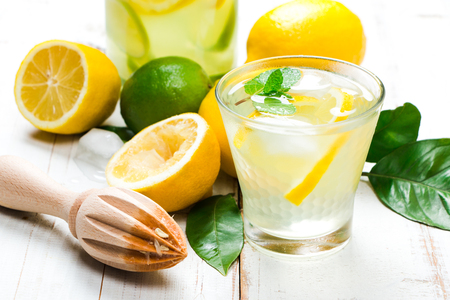 Natural lemonade with lemon, lime and mint with wooden reamer and lemon tree leaves on a white wooden table