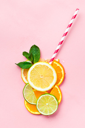 Glass of juice made of citrus slices with mint leaves and a straw on light pink background. Citrus juice concept