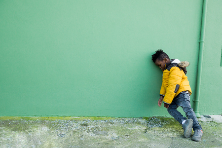 Tired and angry little boy in yellow coat leaning on a green wall on the street