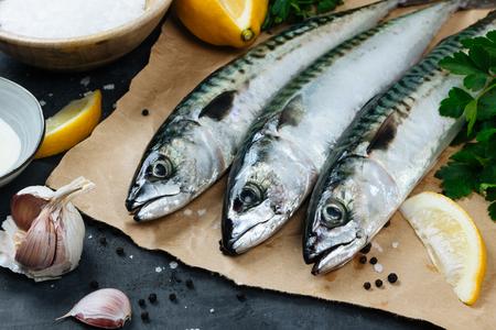 Fresh mackerel fish on paper with lemon, salt, olive oil, garlic, parsley and pepper Stok Fotoğraf