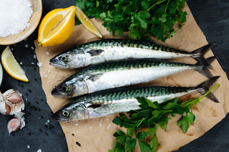 Fresh mackerel fish on paper with lemon, salt, olive oil, garlic, parsley and pepper. Top view Zdjęcie Seryjne