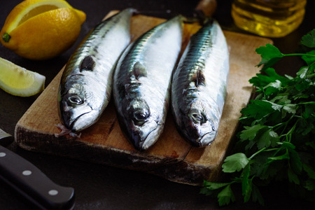 Fresh mackerel fish on cutting board with parsley, lemon and olive oil ready to cook Stok Fotoğraf