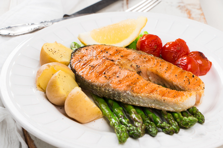 Slice of grilled salmon garnished with cooked potatoes, green asparagus, sauted cherry tomatoes and lemon