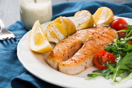 Slice of grilled salmon garnished with cooked potatoes, arugula and cherry tomato salad, yoghurt sauce with herbs and lemon
