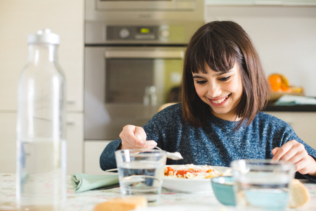 Cute and happy little girl spreading powdered cheese to her dish of pasta in the kitchen at home Stockfoto