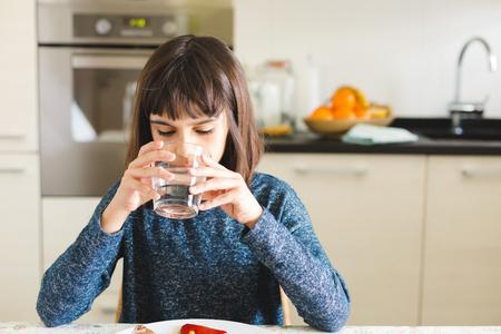 Nettes kleines Mädchen , das Wasser während der Mittagszeit in der Küche zu Hause trinkt Standard-Bild - 99542902