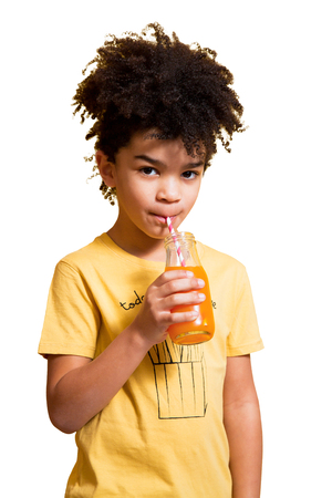 Cute afro little boy drinking orange and carrot juice from a bottle with a straw. Isolated on white Stock Photo