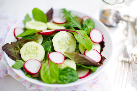 Mixed salad with baby leaves of red lettuce, tatsoi, arugula, red chard, radish and cucumber with olive oil and balsamic vinegar dressing on white background. Selective focus