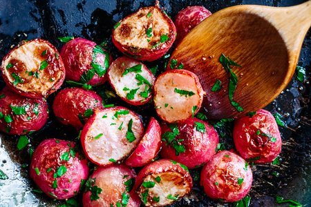 Beautiful roasted radishes in a pan with a wooden spoon close up Stockfoto