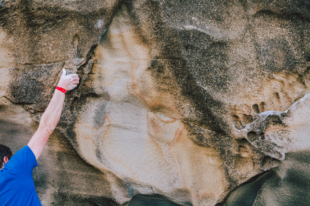Arm of a rock climber man with scars and bounds and red wristband gripping the crack of a wall