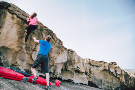 Young couple of climbers assisting eachother to climb the cliff in the coast