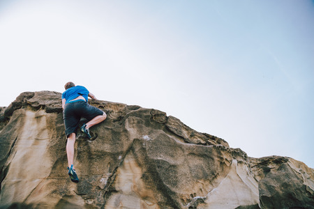 Young rock climber man reaching the top of the wall