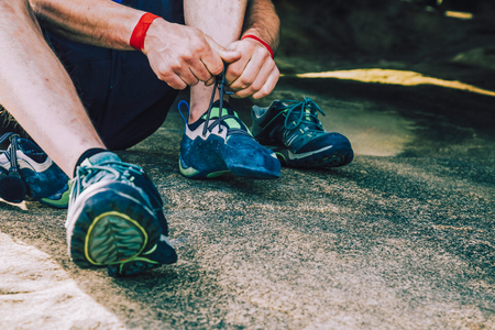 Close up of rock climber man with wristbands putting climbing shoes on sitting on a rock