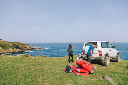 Couple of climbers with dog taking the equipment out of the car in the coast Stock Photo