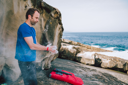 Young climber man coating his hands in powder chalk magnesium for climbing in the coast Stock Photo