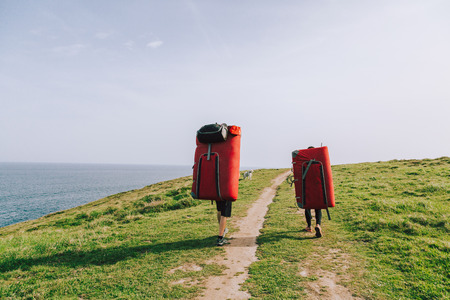 Couple of climbers with dog hiking with crash pads on the back to climb at the coast
