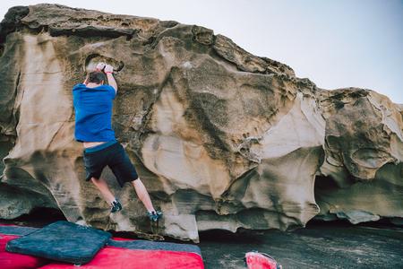 Rock climbing man starting the climb of a wall