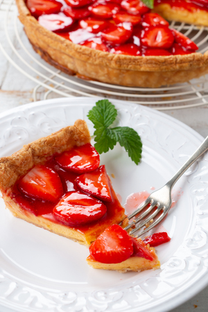 Homemade strawberry tart decorated with strawberry leaves and portion in a plate Stock Photo