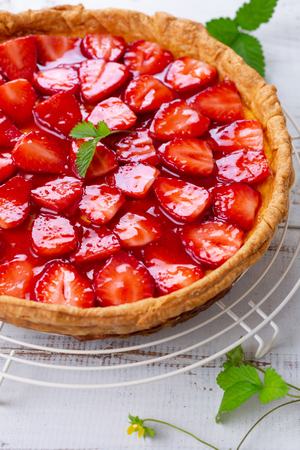 Homemade strawberry tart decorated with strawberry leaves Stock Photo