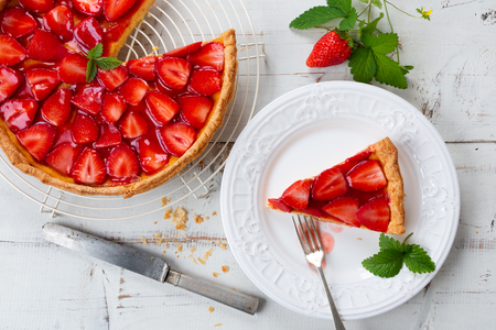 Homemade strawberry tart decorated with strawberry leaves and portion in a plate. Top view