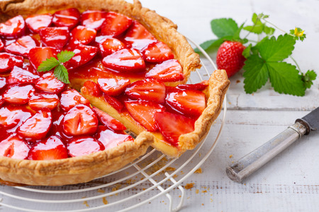 Homemade strawberry tart decorated with strawberry leaves close up