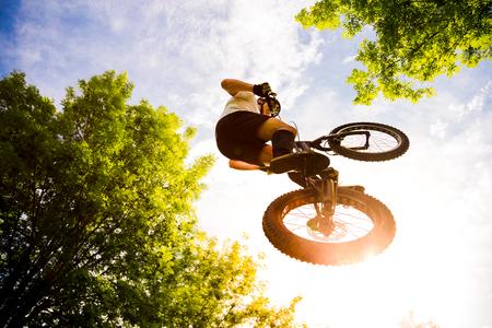 Jonge fietser die met zijn proeffiets in het bos bij zonsondergang vliegt. Extreem lage kijkhoek