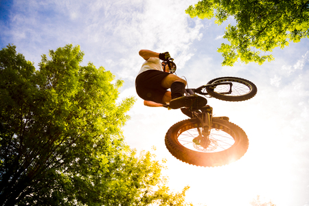 Young cyclist flying with his trial bycicle  in the forest at sunset. Extreme low angle view Stock Photo