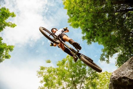 Jonge fietser die met zijn fiets van een rots in het bos vliegt. Extreem lage kijkhoek