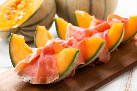 Melón cantalupo con jamón, un aperitivo tradicional español e italiano Foto de archivo
