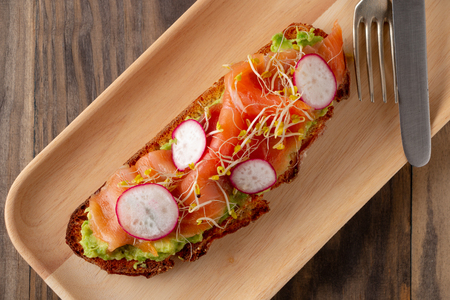 Rustic bread toast with mashed avocado, smoked salmon, radish, broccoli and sprouts served in a wooden plate on a rustic wooden table. Top view