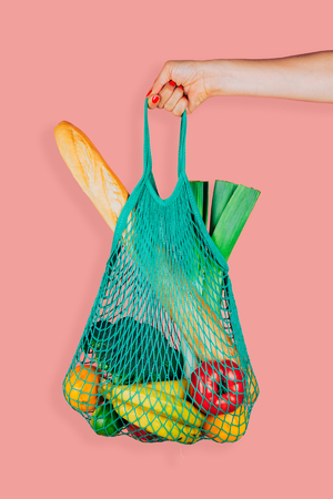 Woman hand holding a green mint string shopping bag with vegetables, fruits and bread in front of a pink background