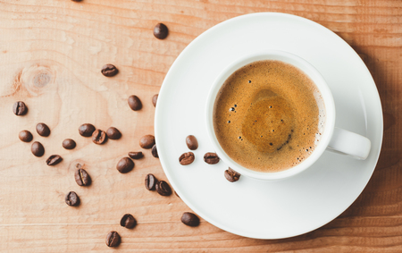 Cup of coffee and roasted coffee beans on rustic wooden background. Top view, flat lay Standard-Bild - 103844365