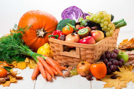 Assortment of fresh and ripe autumn vegetables and fruits on a rustic wooden table isolated on white