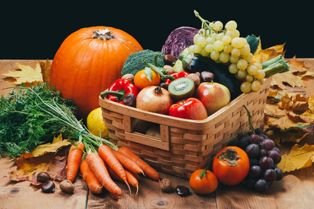 Assortment of fresh and ripe autumn vegetables and fruits on a rustic wooden table with black background
